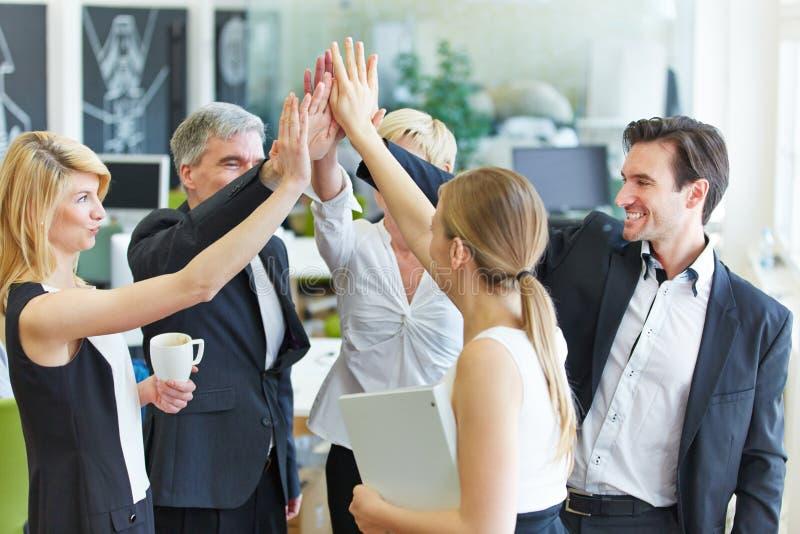Équipe d'affaires faisant la haute cinq dans le bureau photographie stock