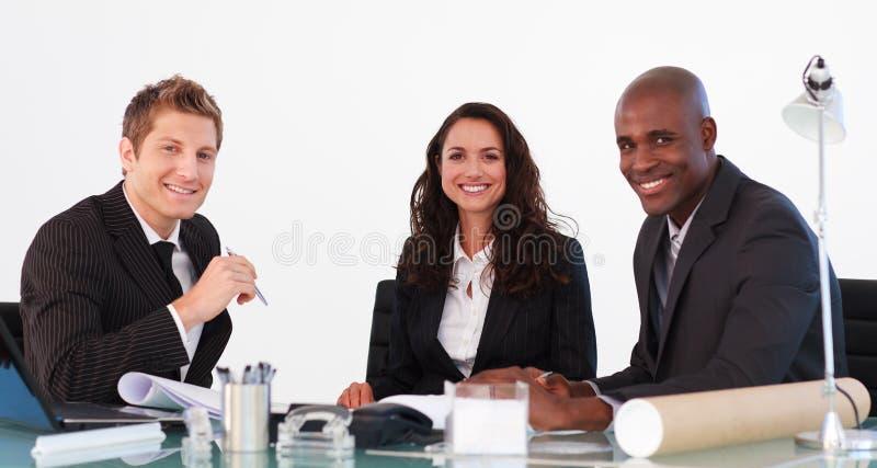 Équipe d'affaires lors d'un contact regardant l'appareil-photo photographie stock