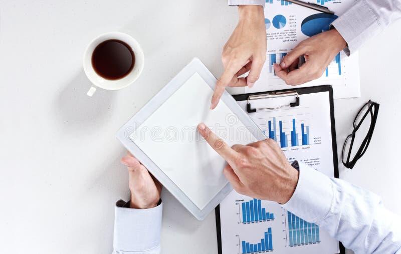 Équipe d'affaires lors de la réunion utilisant le PC de pavé tactile de comprimé photos stock