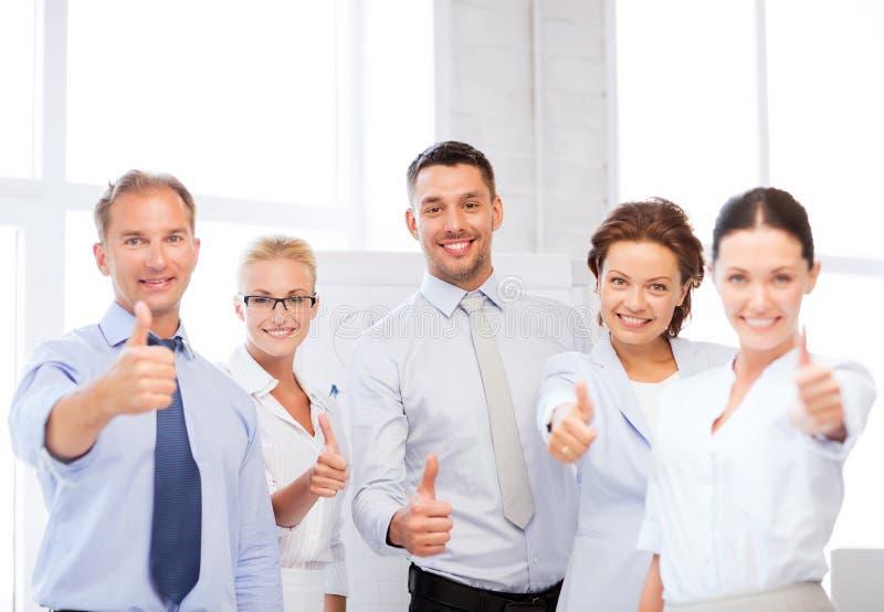 Équipe d'affaires montrant des pouces dans le bureau images libres de droits