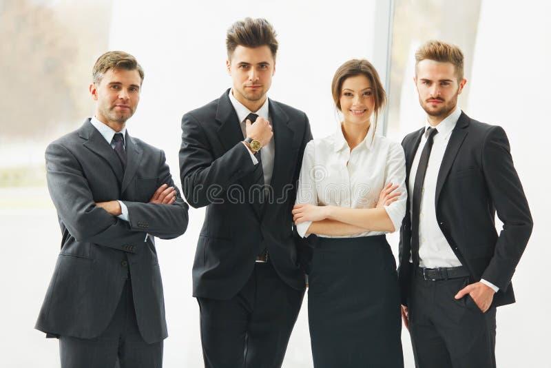 Équipe d'affaires Personnes de sourire heureuses se tenant dans une rangée au bureau photos stock