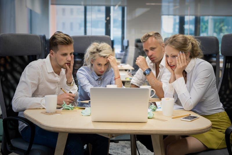Équipe d'affaires regardant l'ordinateur avec des expressions choquées photos libres de droits
