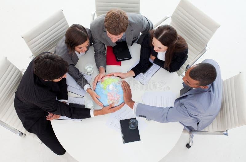 Équipe d'affaires retenant un globe terrestre images stock
