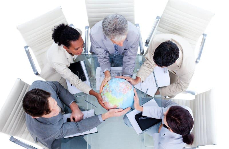 Équipe d'affaires retenant un globe terrestre image stock