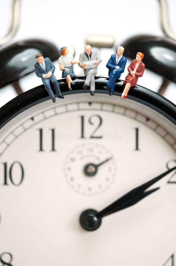 Équipe d'affaires s'asseyant sur l'horloge géante photographie stock libre de droits