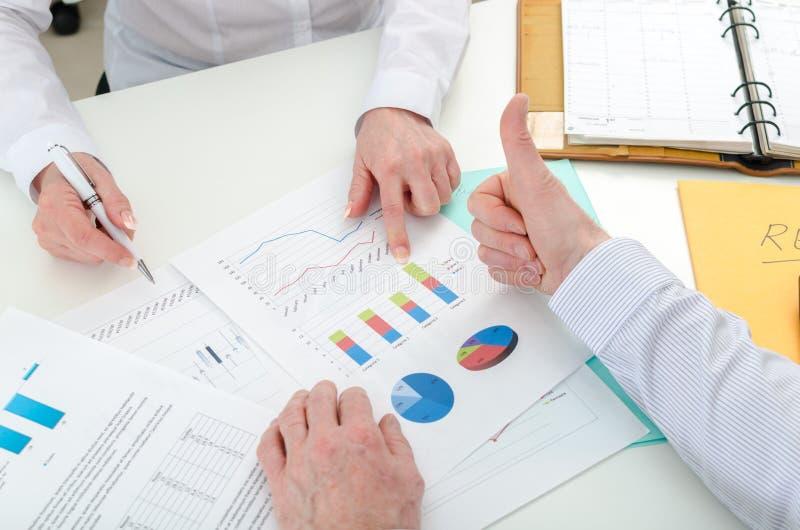 Équipe d'affaires satisfaite au sujet des bilans financiers photographie stock