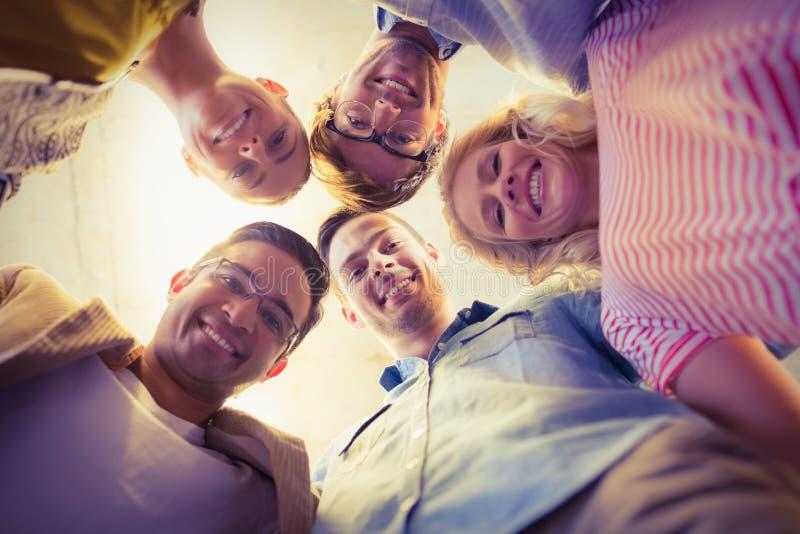 Équipe d'affaires se tenant en cercle souriant à l'appareil-photo photos libres de droits
