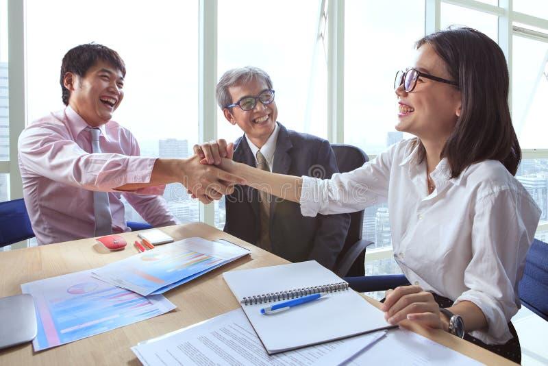 Équipe d'affaires serrant la main et riant le bonheur pour réussi images stock
