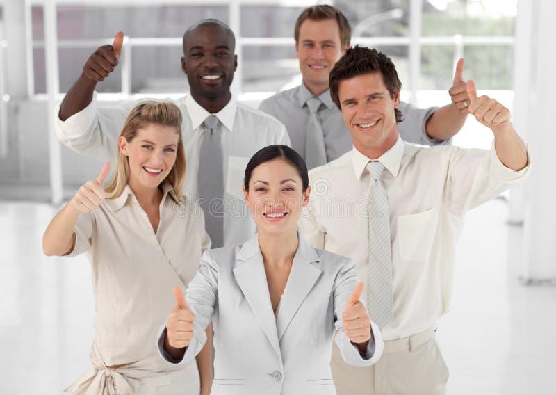 Équipe d'affaires souriant supportant des pouces image stock