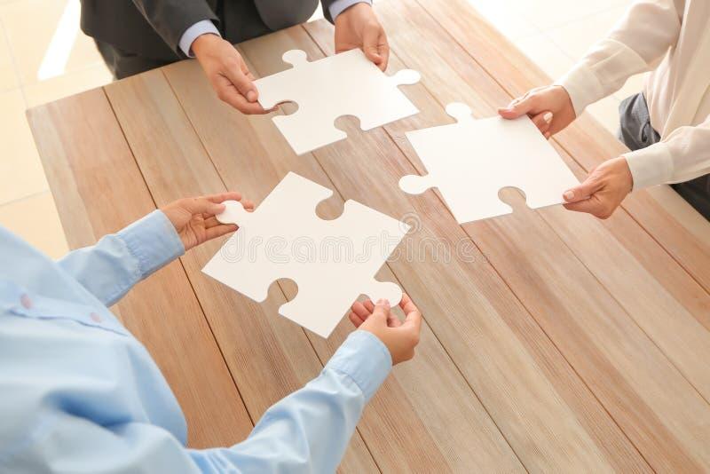 Équipe d'affaires tenant des morceaux de puzzle au-dessus de table en bois, plan rapproché image libre de droits