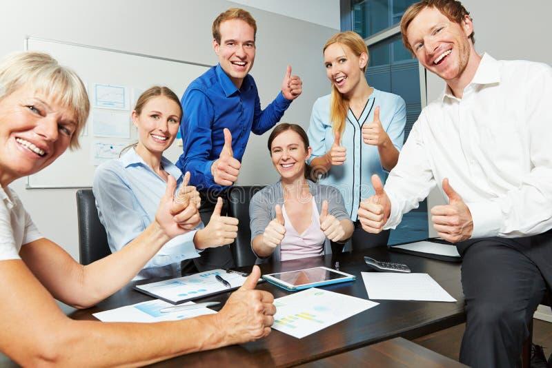 Équipe d'affaires tenant des pouces dans le bureau photos libres de droits