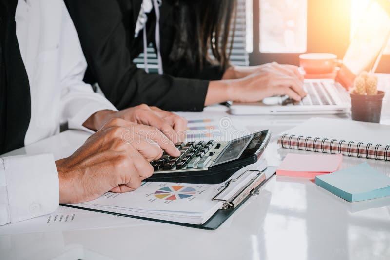 Équipe d'affaires utilisant la calculatrice et l'ordinateur portable à travailler avec des données financières photo stock