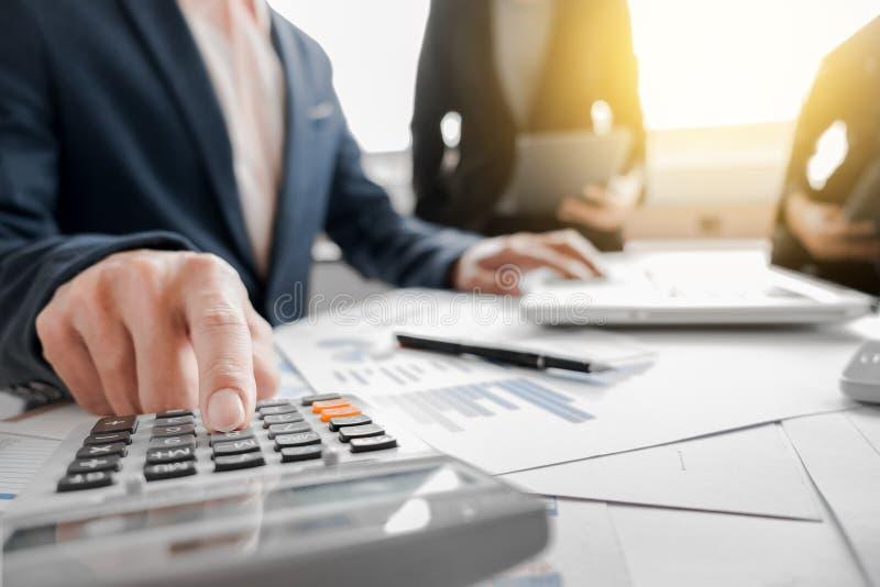 Équipe d'affaires utilisant une calculatrice pour calculer les nombres sur le sien photo stock
