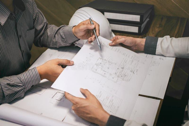Équipe d'ingénierie de construction ou associé d'architecte discuter un modèle tout en vérifiant l'information sur dessiner et es photographie stock