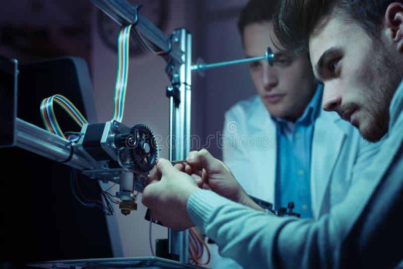 Équipe d'ingénierie travaillant à une imprimante 3D photos stock