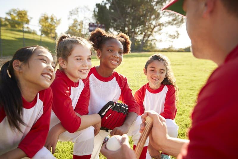 Équipe de baseball de fille dans un petit groupe d'équipe avec l'entraîneur, écoutant photographie stock