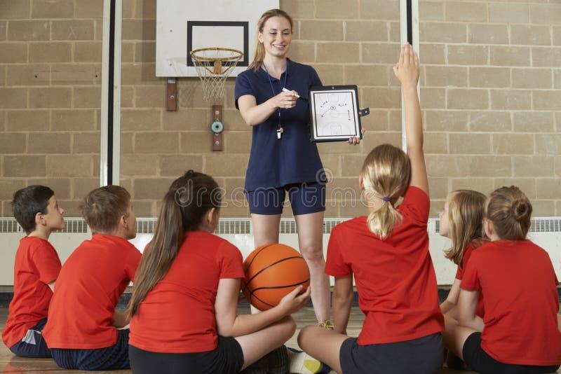 Équipe de basket de Giving Team Talk To Elementary School d'entraîneur photographie stock libre de droits