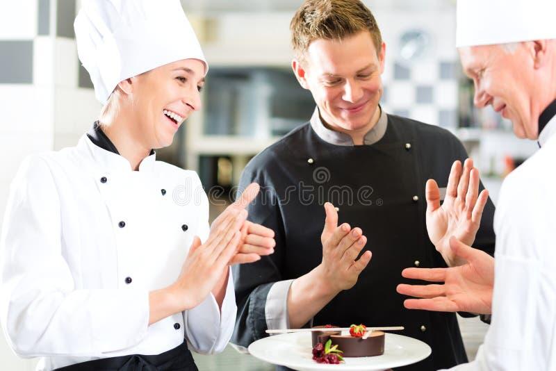 Équipe de chef dans la cuisine de restaurant avec le dessert photographie stock