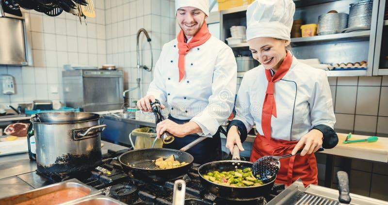 Équipe de chefs dans une cuisine préparant une cuisine fantastique dans des casseroles image libre de droits