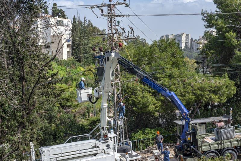 Équipe de compagnie d'électricité travaillant à une tour de transmission utilisant deux ascenseurs de camion photo stock