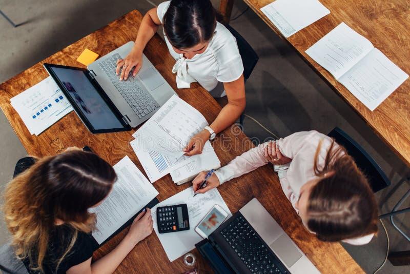 Équipe de comptables féminins établissant le rapport financier annuel fonctionnant avec des papiers utilisant des ordinateurs por photos stock