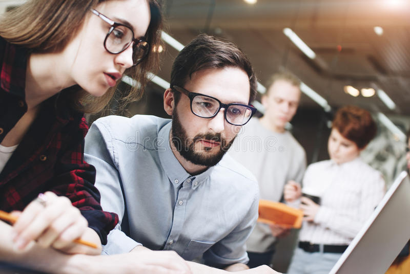Équipe de Coworking travaillant sur un nouveau projet Carnet contemporain sur la table en bois dans un bureau moderne de grenier images stock