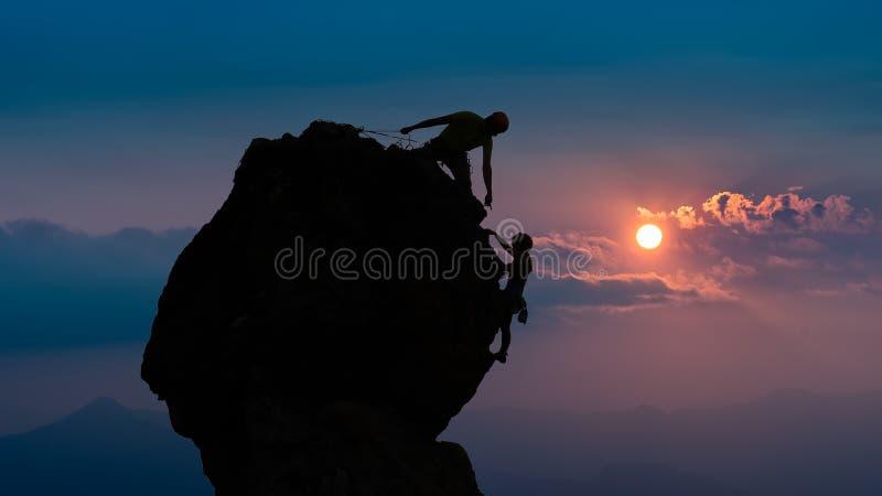 Équipe de deux alpinistes roped dedans pour vous aider à conquérir la crête photographie stock