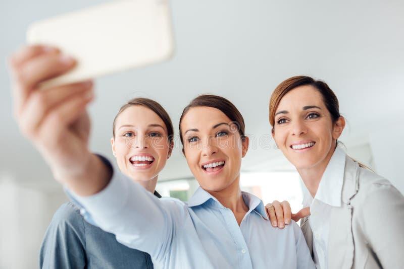 Équipe de femmes de sourire d'affaires prenant un selfie photos stock