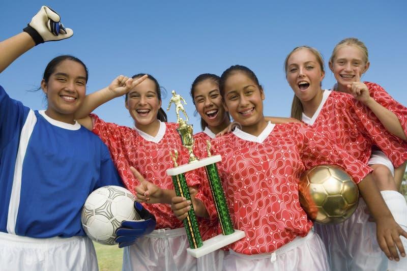 Équipe de football féminine tenant le trophée photographie stock libre de droits