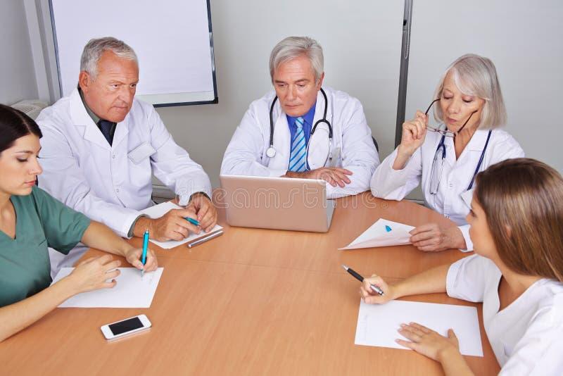 Équipe de médecins lors d'une réunion de groupe photos libres de droits