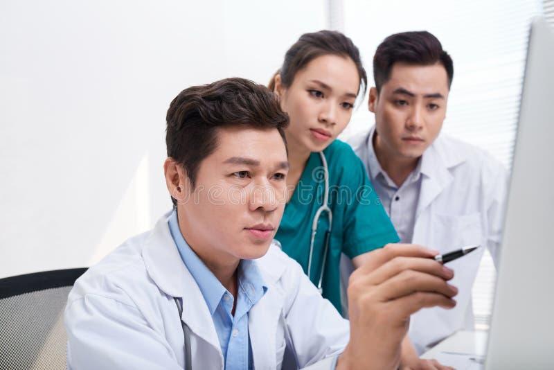 Équipe de médecins travaillant et ayant sur l'ordinateur portable dans le bureau médical images libres de droits