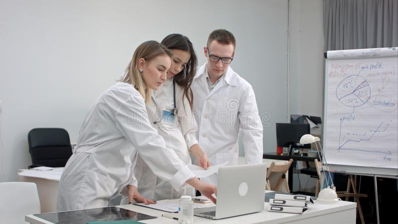 Équipe de médecins travaillant sur l'ordinateur portable et analysant le rayon X dans le bureau médical image libre de droits
