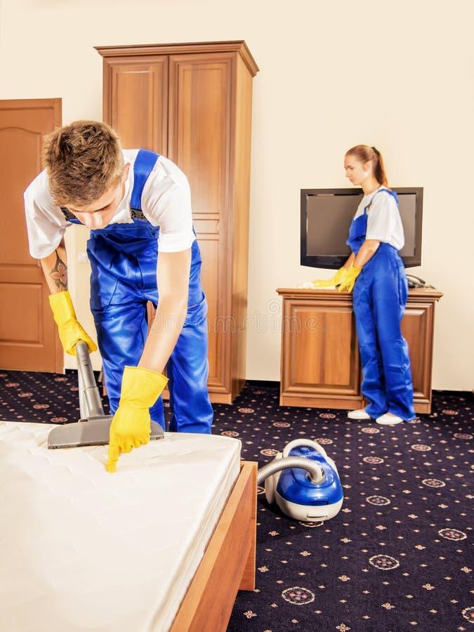 Équipe de nettoyage dans l'uniforme fonctionnant dans la chambre photo libre de droits