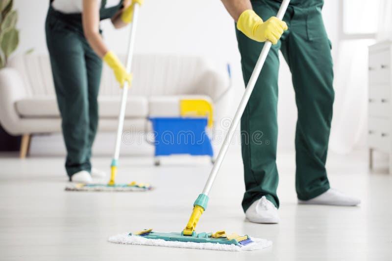 Équipe de nettoyage essuyant le plancher images libres de droits