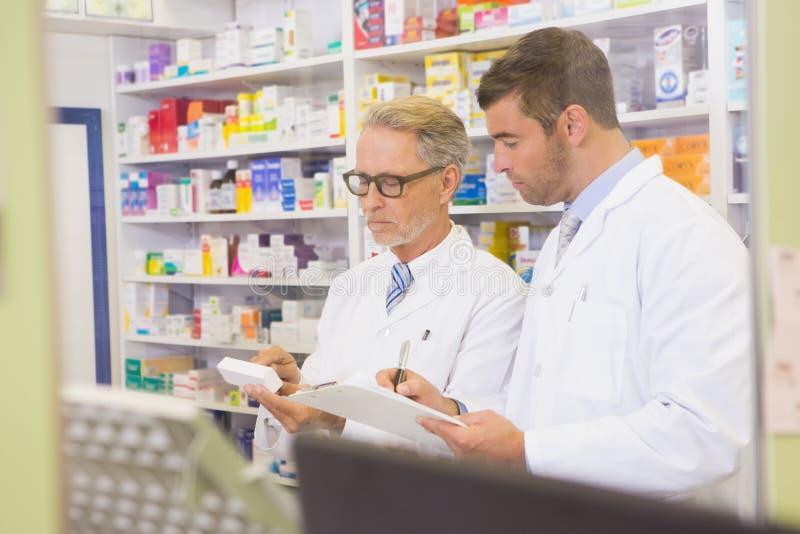 Équipe de pharmaciens écrivant sur le presse-papiers photos stock