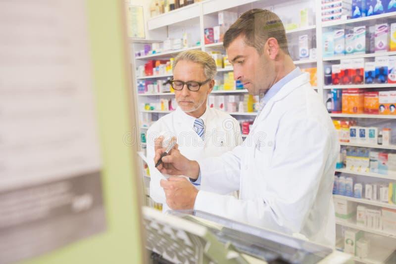 Équipe de pharmaciens écrivant sur le presse-papiers photographie stock