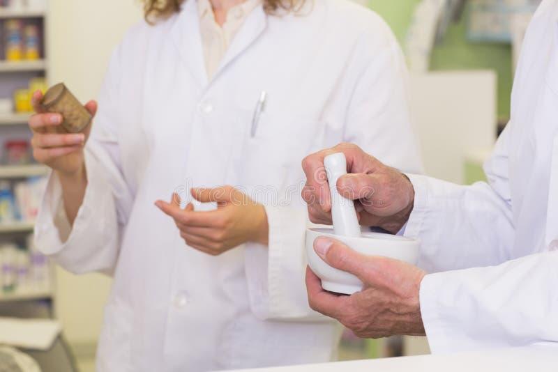 Équipe de pharmaciens tenant les médecines et le mortier photo stock