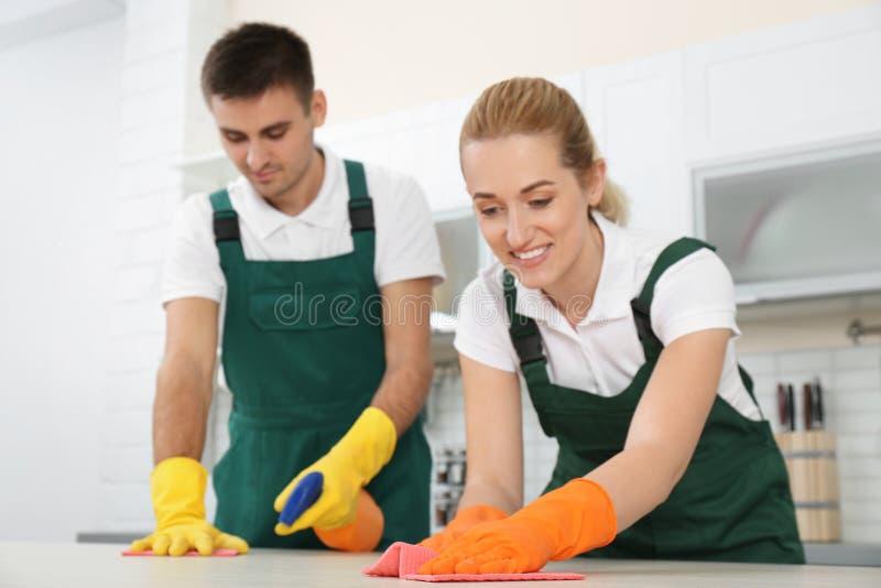 Équipe de portiers nettoyant la table photographie stock