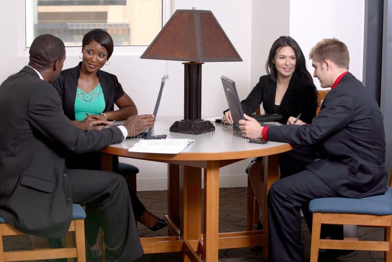 Équipe de quatre fonctionnant à la table image stock