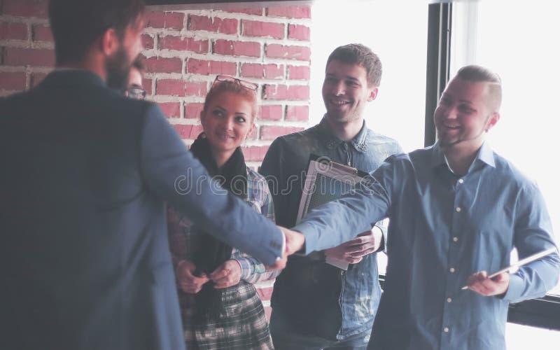 Équipe de redacteurs publicitaires et une poignée de main des associés dans un bureau créatif images stock
