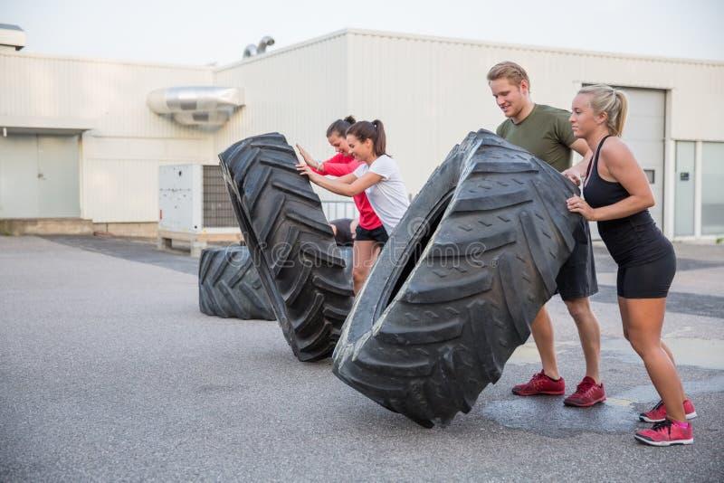 Équipe de séance d'entraînement renversant des pneus extérieurs photos stock