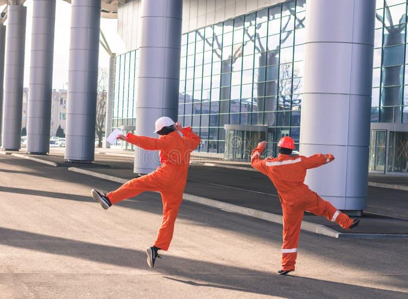 Équipe de sauter heureux de jeunes ingénieurs après travail lourd photographie stock