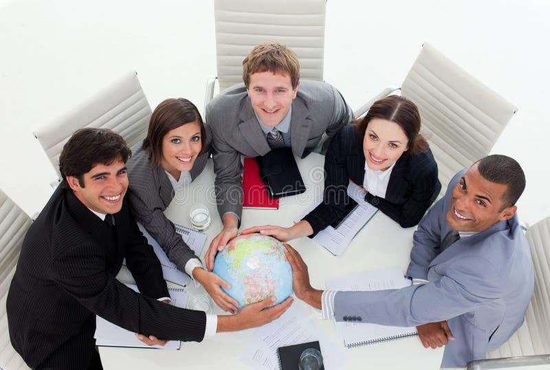 Équipe de sourire d'affaires retenant un globe terrestre images libres de droits