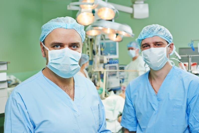 Équipe de sourire de chirurgiens à l'opération cardiaque de chirurgie photographie stock libre de droits
