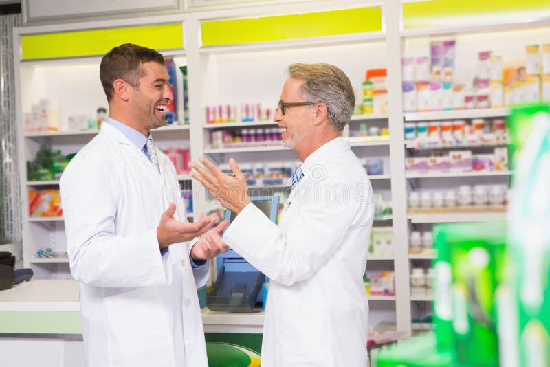 Équipe de sourire de pharmacien parlant ensemble photos stock