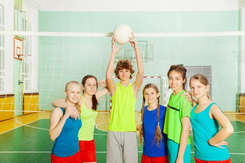 Équipe de volleyball se tenant avec la boule à côté du filet photographie stock