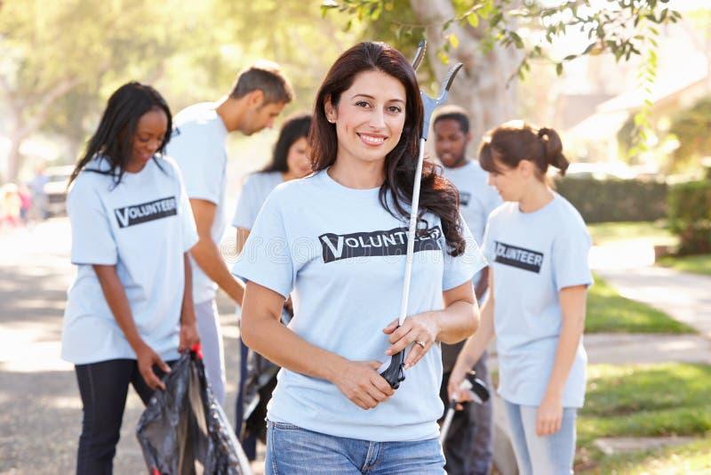 Équipe de volontaires prenant des ordures dans la rue suburbaine images stock