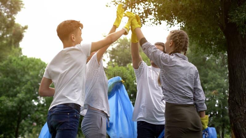 Équipe de volontaires salut-fiving pendant le rassemblement des déchets en parc, nature de sauvegarde photographie stock libre de droits