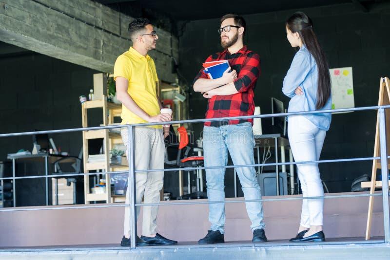 Équipe des jeunes créatifs parlant dans le bureau images libres de droits