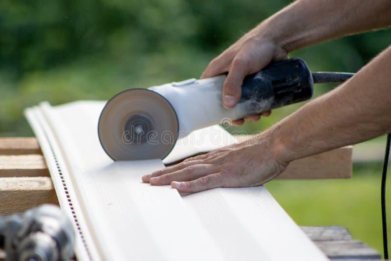 Équipe des mains tenant la broyeur d'angle, dispositif électrique avec le disque, coupant le matériel de voie de garage pour des  images libres de droits